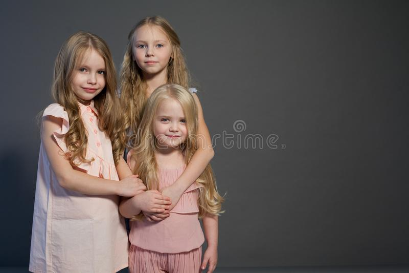 Three beautiful little girls sisters portrait fashion grey background stock images