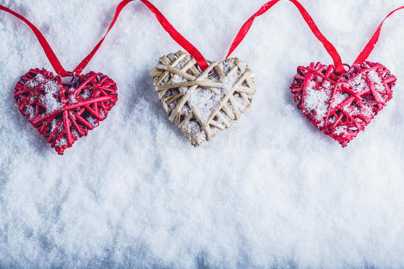 Three beautiful romantic vintage hearts are hanging on a red band on a white snow background. Love and St. Valentines Day concept. Three beautiful romantic stock photos