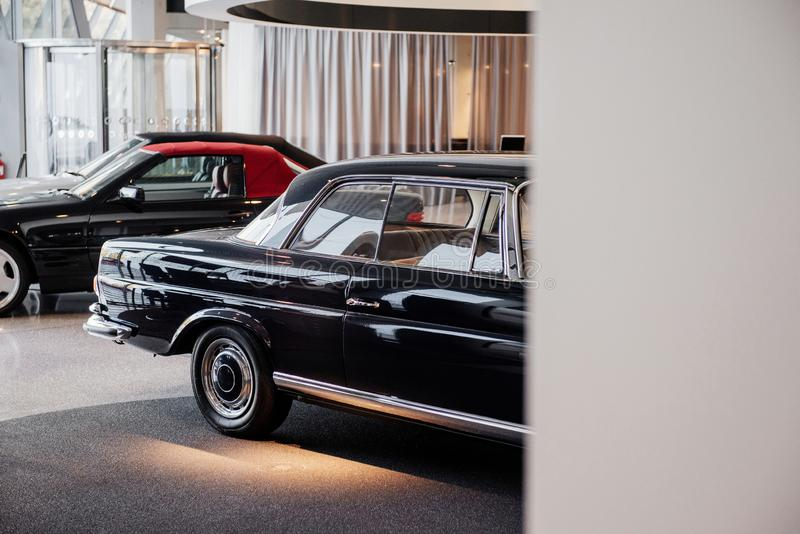 Three beautiful shining polished cars parked indoors at automobile exhibition.  royalty free stock image