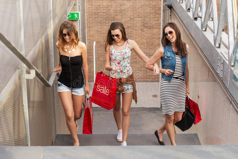 Three beautiful woman walks up the stairs, they go shopping royalty free stock photo