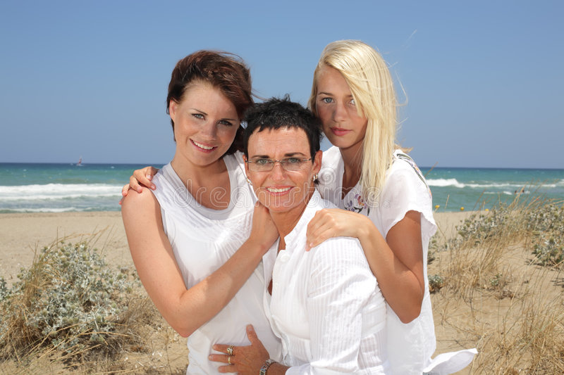 Three beautiful women on the beach. Beautiful mother and daughters on the beach royalty free stock photos