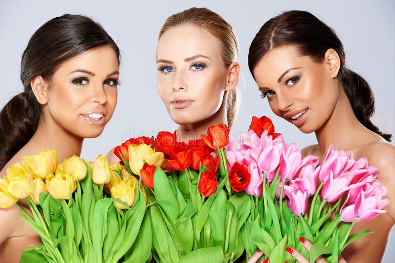 Three beautiful women with fresh spring tulips. Three beautiful topless women with bunches of fresh spring tulips held to their chests smiling at the camera royalty free stock image