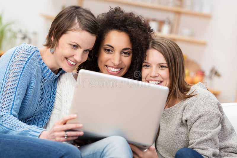 Three beautiful women with a laptop computer royalty free stock image