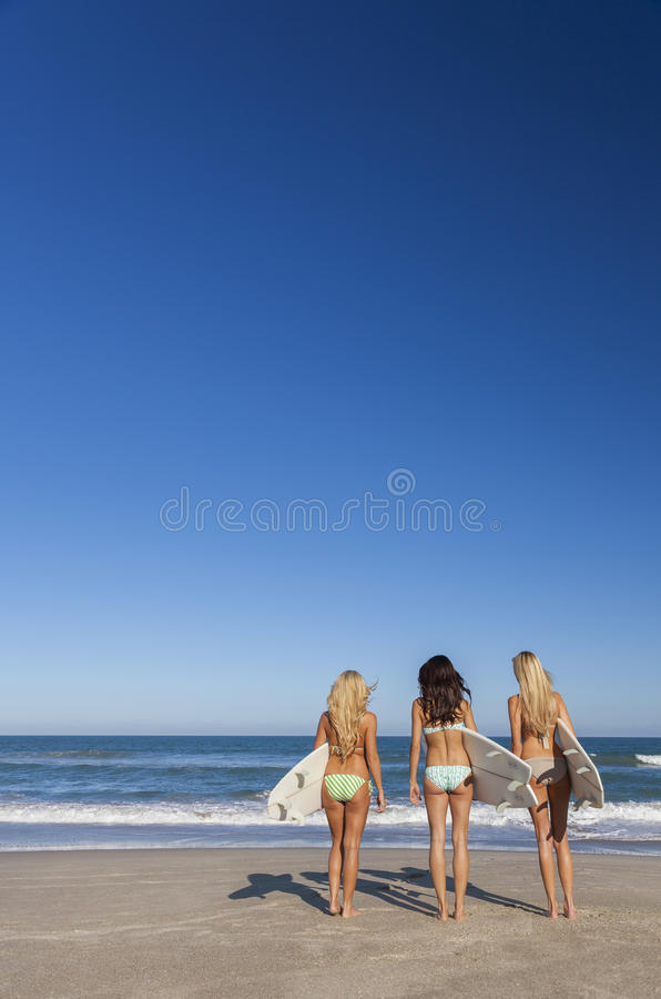 Three Beautiful Women Surfers In Bikinis With Surfboards At Beach stock photography