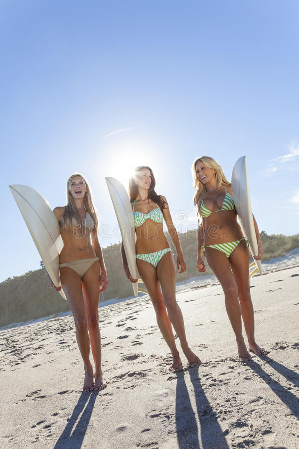 Three Beautiful Women Surfers In Bikinis With Surfboards At Beach royalty free stock photography