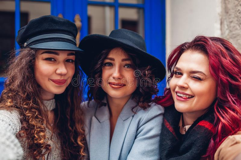 Three beautiful women taking selfie on city street. Friends hanging and having fun. Three beautiful women taking selfie on city street. Happy friends hanging and royalty free stock photos