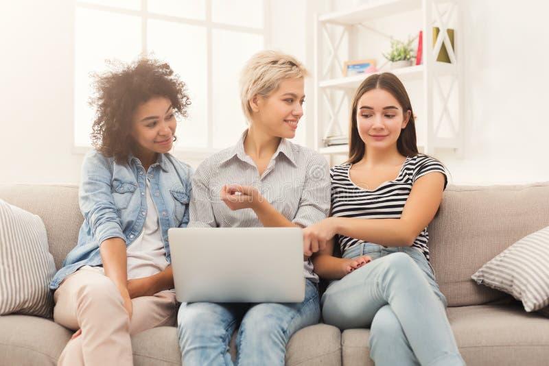Three beautiful women using laptop at home stock image