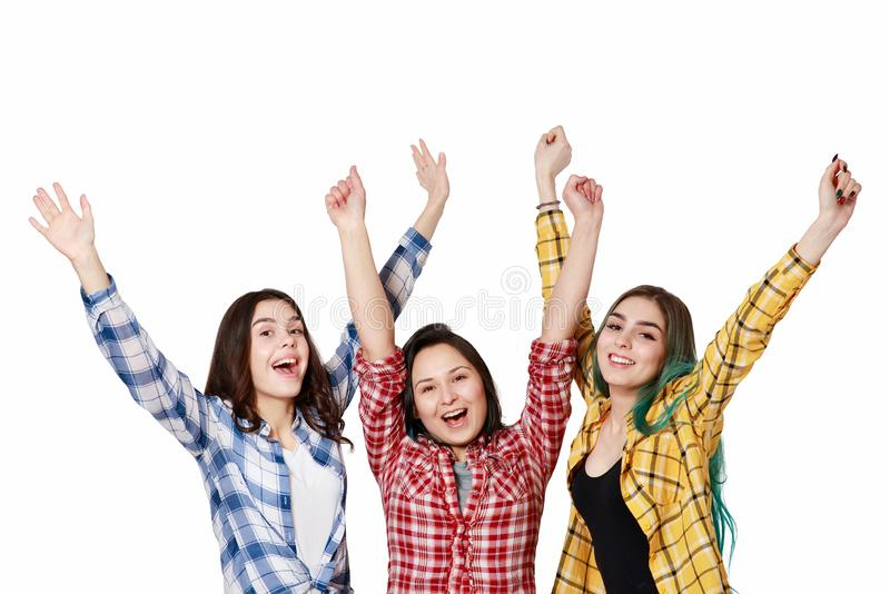 Three beautiful young girls with their hands up happily. isolated on white background With copyspace stock photos