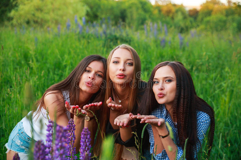 Three beautiful young happy girls best friends send an air kiss having fun, smiling and laughing. Friendship concept. stock image
