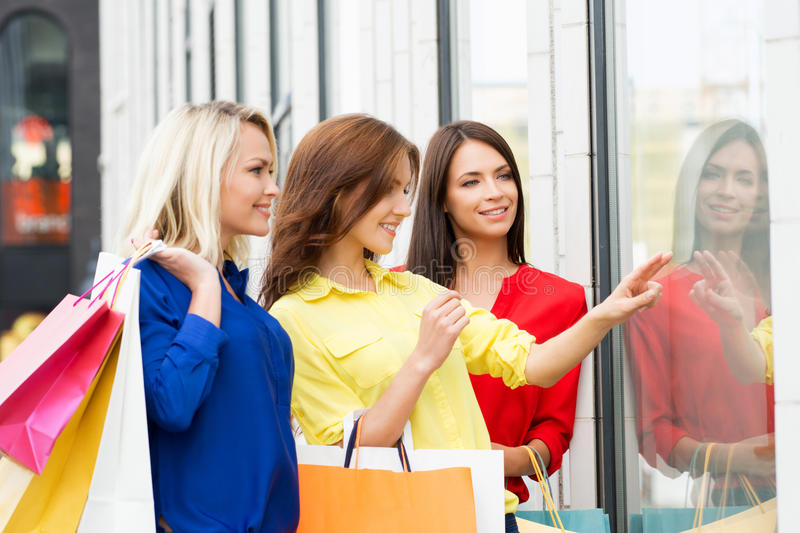 Three beautiful young happy women with shopping bags. Watching a showcase royalty free stock photography