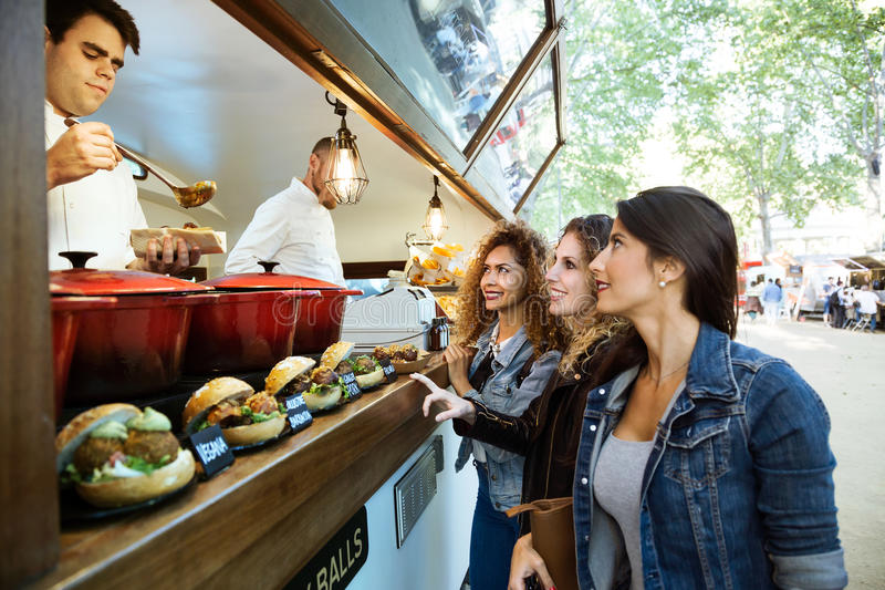 Three beautiful young women buying meatballs on a food truck. Portrait of three beautiful young women buying meatballs on a food truck in the park stock image