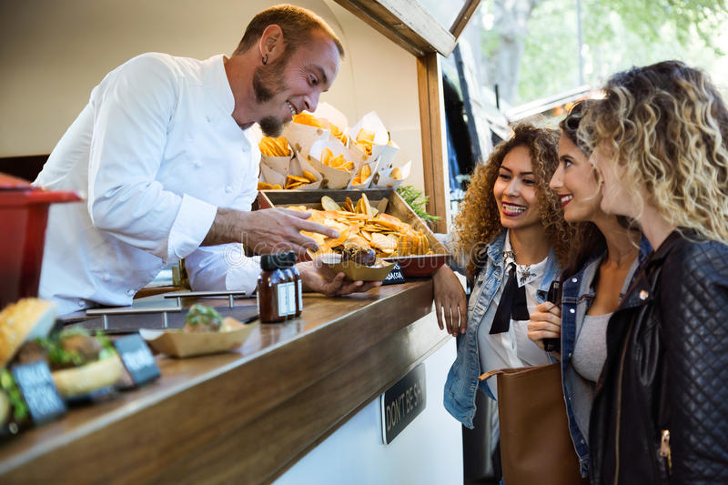 Three beautiful young women buying meatballs on a food truck. royalty free stock photography