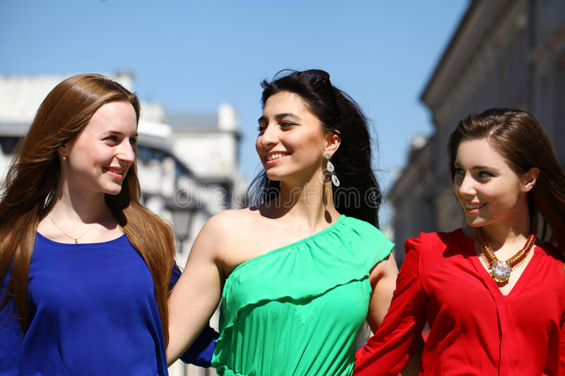 Three Beautiful young women in colorful dress stock photos