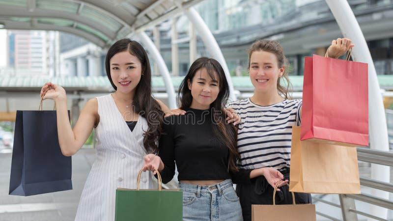 Three beautiful young women enjoying shopping in the city stock images