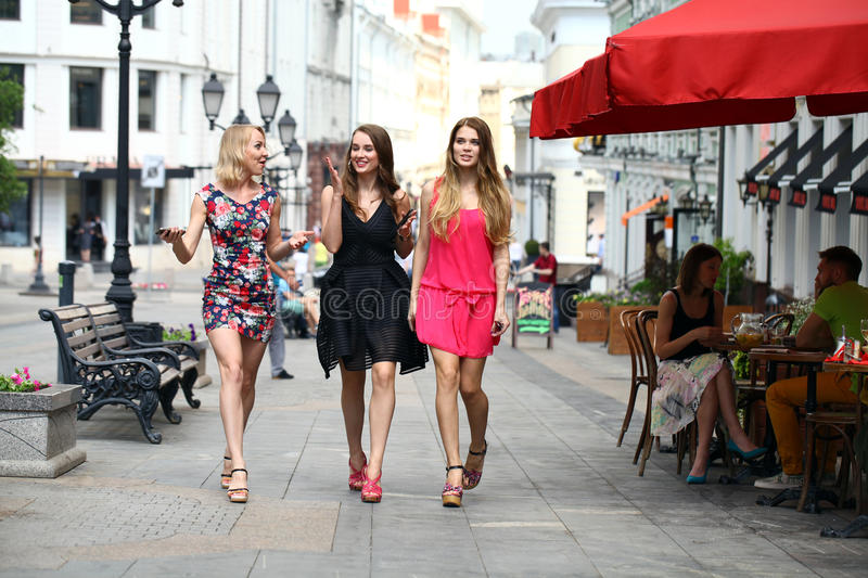 Three beautiful young women girlfriends walk on a summer street. In the city center stock image