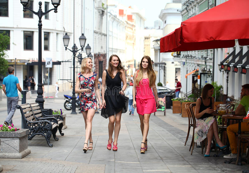 Three beautiful young women girlfriends walk on a summer street. In the city center royalty free stock photo