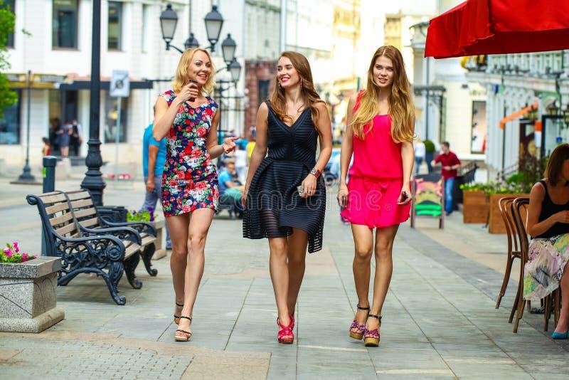 Three beautiful young women girlfriends walk on a summer street. In the city center stock photos