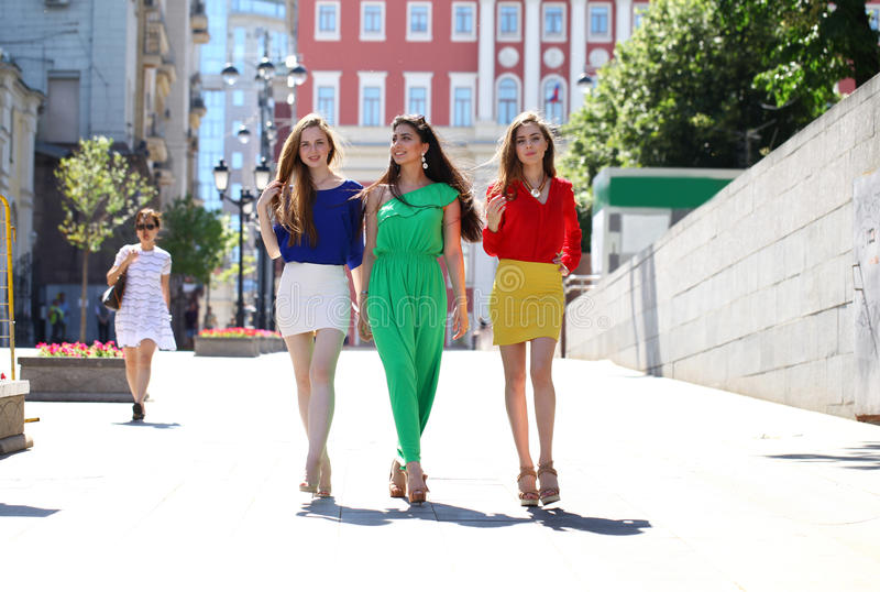 Three beautiful young women girlfriends walk on a summer street. In the city center royalty free stock photos