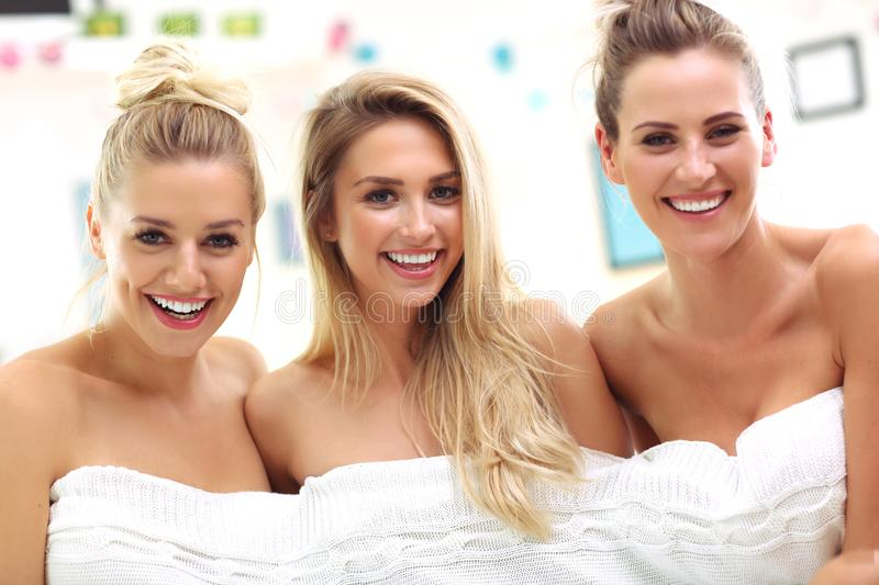Three beautiful young women in home spa. Picture of three beautiful young women in white towels at home royalty free stock photo
