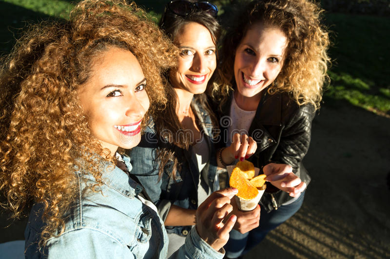 Three beautiful young women visiting eat market in the street. Portrait of three beautiful young women visiting eat market in the street royalty free stock photos
