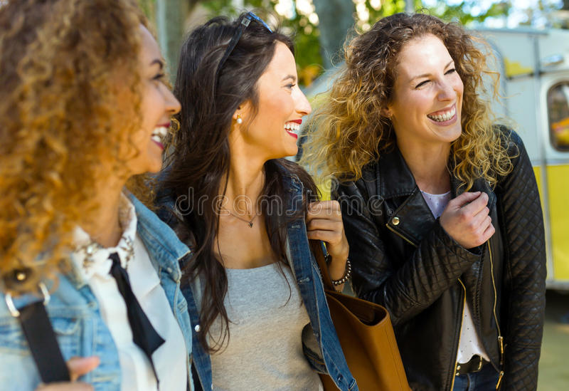Three beautiful young women walking and talking in the street. royalty free stock photography