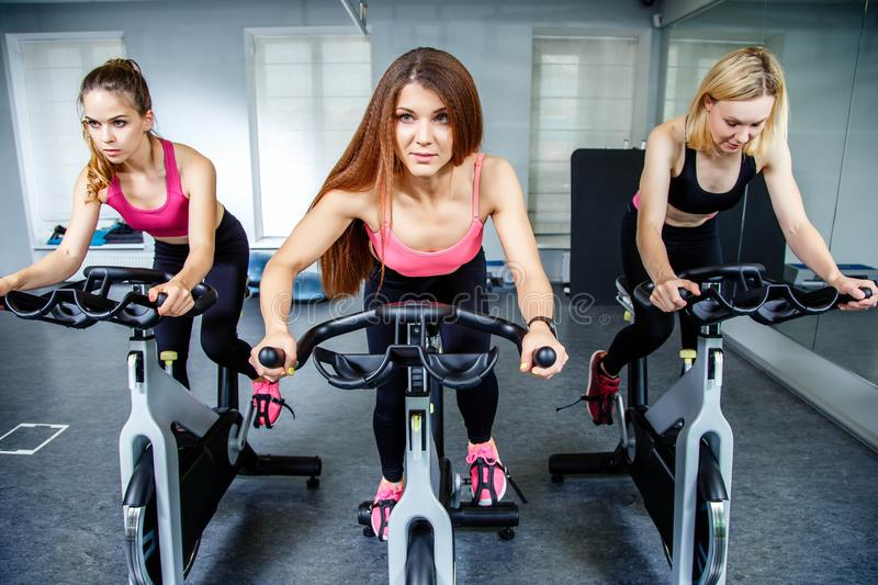 Three beautiful young women working out on bikes at the gym. stock photos