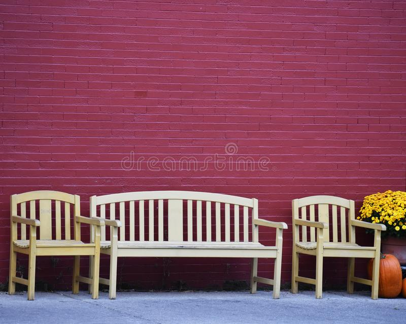 Three bench seats with mums and pumpkins royalty free stock images
