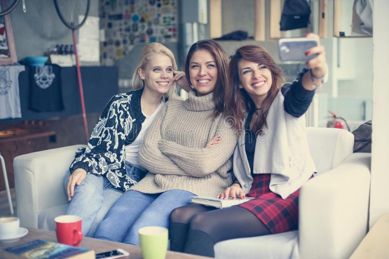 Three best friends in a cafe. Young women making self-picture. royalty free stock image