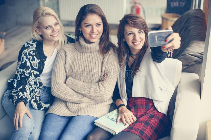 Three best friends in a cafe. Young women making self-picture. royalty free stock images