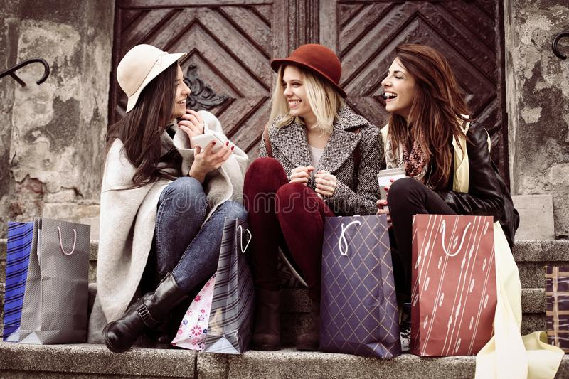 Three best friends enjoying after shopping. Young girls sitting royalty free stock photography