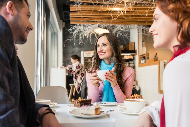 Three best friends relaxing together with cakes and coffee royalty free stock photo