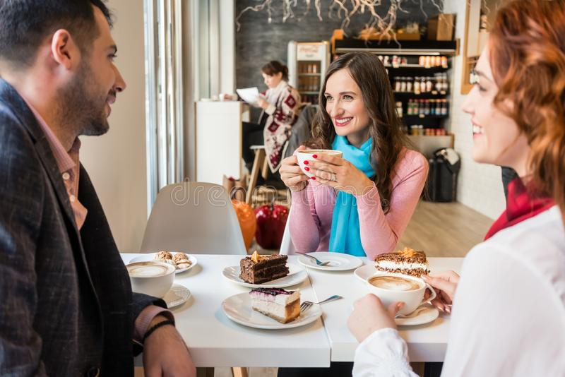 Three best friends relaxing together with cakes and coffee stock image