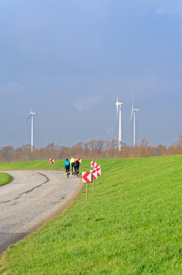 Bicycle riders on a country road and wind turbines on the blue sky in the background. Three bicycle riders on a country road and wind turbines on the blue sky in stock image