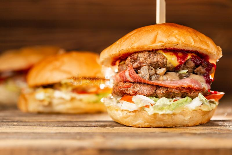 Three big burger with meat cooked on BBQ coal. Lunch on a wooden background. The concept of fast food and unhealthy food. Three big burger with meat cooked on royalty free stock photo