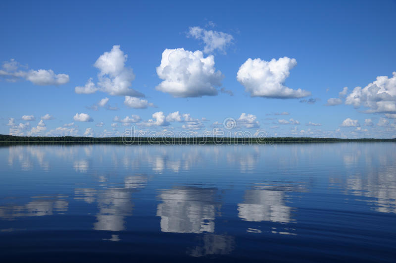 Download Three Big Clouds Above The Mirrored Lake Stock Image - Image: 10635009