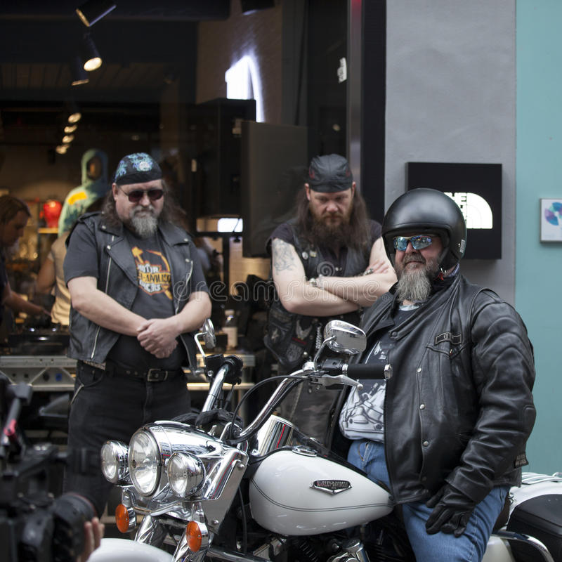 Three bikers with a motorcycle pose stock image