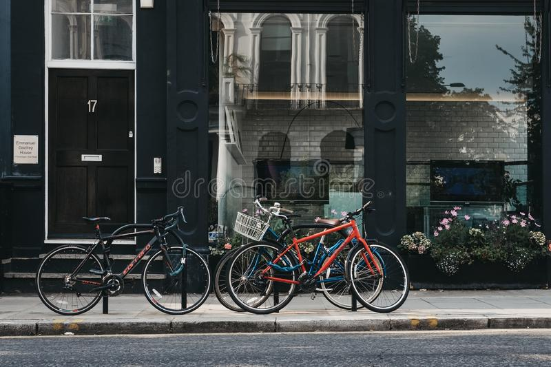 Three bikes parked on the street in London, UK. London, UK - July 21, 2018: Three bikes parked on the street in London, UK. Cycling is a popular mode of stock images