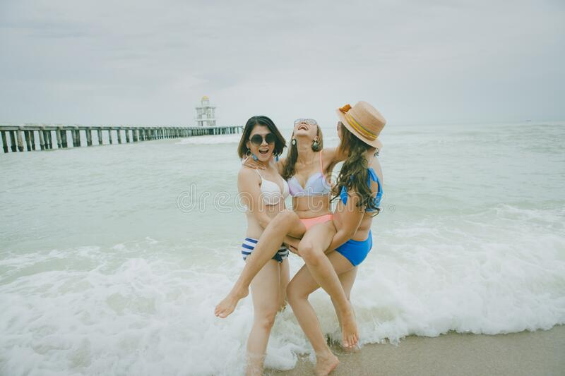 Three bikini asian woman happiness with relaxing emotion in vacation sea beach royalty free stock images