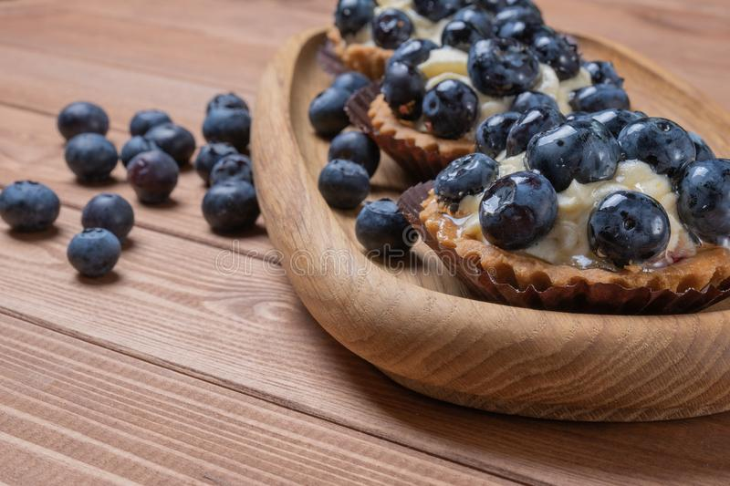 Three bilberry tartlet on a wooden plate on the table, bilberry baked shells, fruit cupcake with blueberry royalty free stock photos