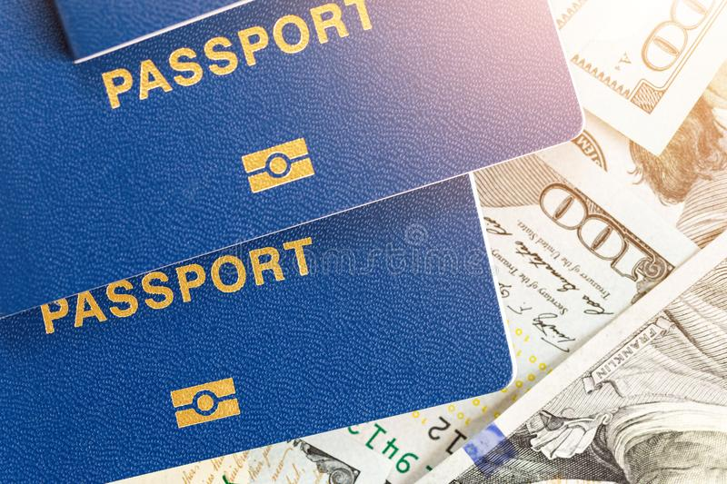 Three biometrical international passports over money background. Blue travel documents lying on US one hundred dollar banknotes. F. Amily tourism and travelling stock images