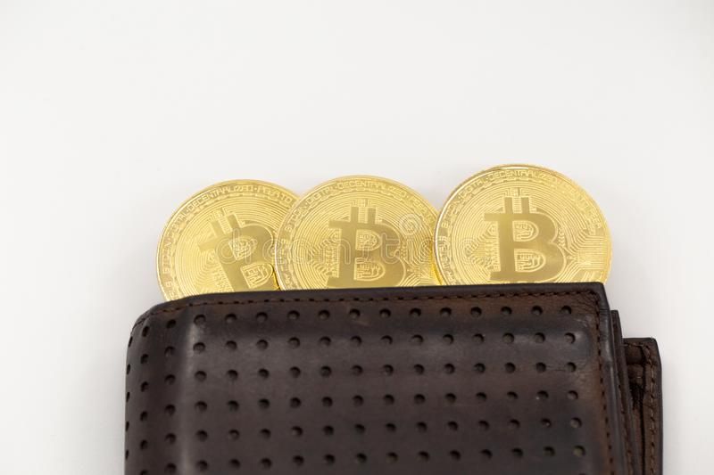 Three Bitcoin tokens coming out of a wallet, on white background. Cryptocurrency in real life concept with copy space stock image