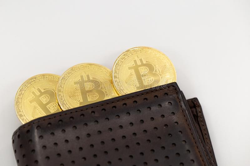 Three Bitcoin tokens coming out of a wallet, on white background. Cryptocurrency in real life concept with copy space royalty free stock image