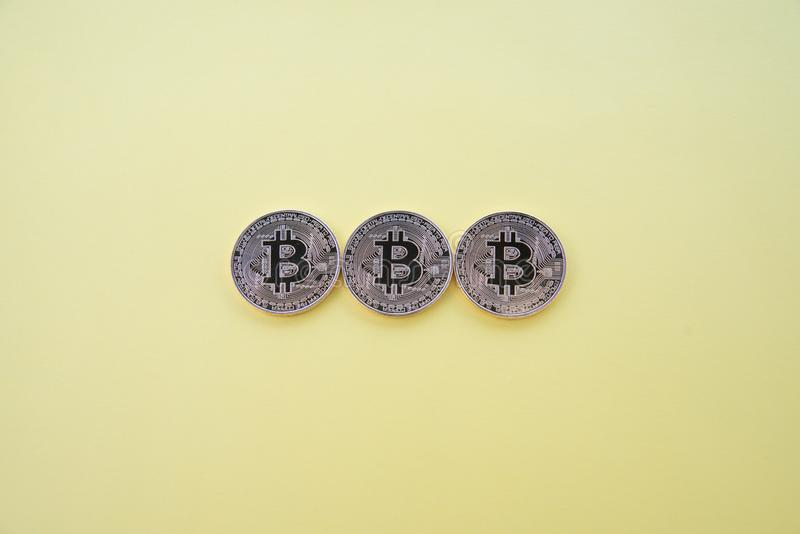 Three Bitcoins on yellow surface centered royalty free stock photography