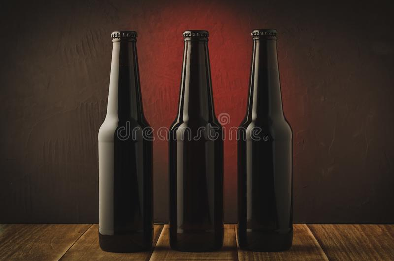 Three black bottle of beer on a red background of a wooden shelf/Three black bottle of beer on a red background of a wooden shelf stock photography