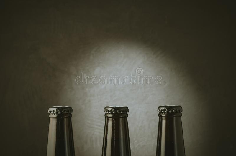three black bottles of beer on a dark background with light/three black bottles of beer on a dark background with light. Copy royalty free stock images