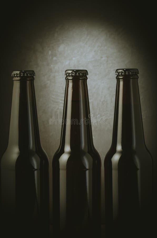 three black bottles of beer on a dark background with light/three black bottles of beer on a dark background with light. Selective royalty free stock image