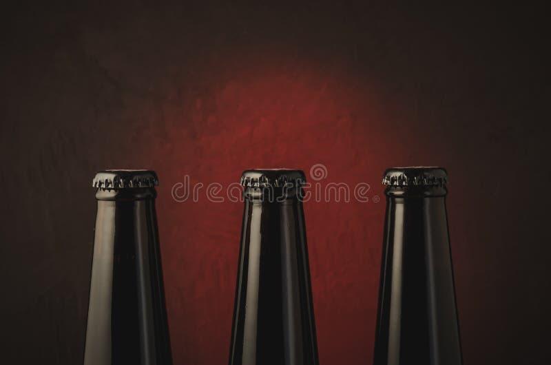 Three black bottles of beer on a dark background with red light/three black bottles of beer on a dark background with red light. stock photo