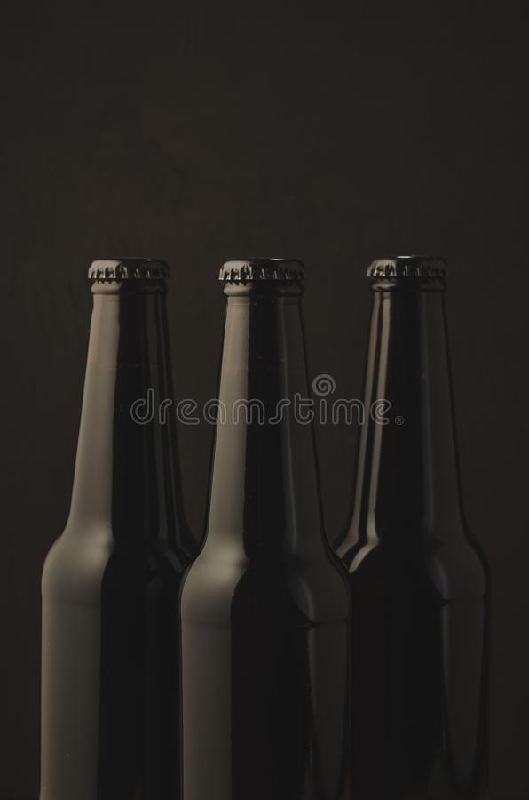 Three black bottles of beer on a dark background/Three black bottles of beer on a dark background, selective focus stock photography