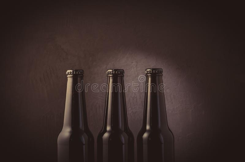 three black bottles of beer on a dark background/three black bottles of beer on a dark background with light. Selective focus stock photography
