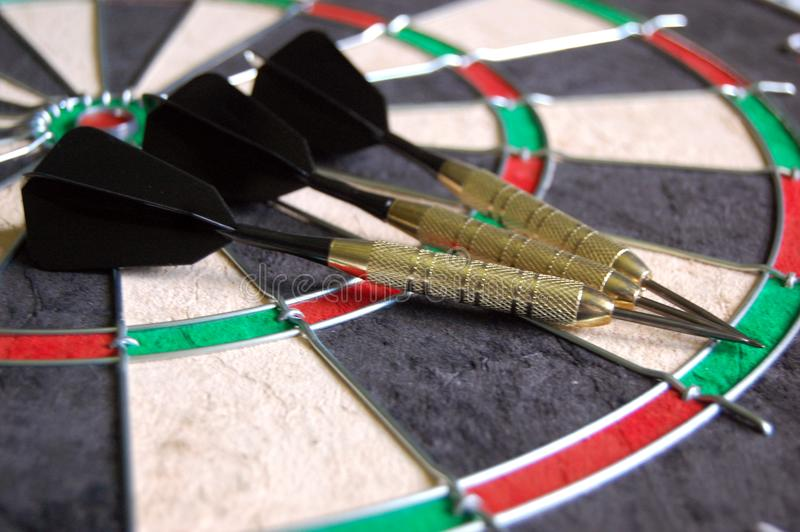 Darts on a Dartboard. Three black and gold darts laying on a new dartboard royalty free stock photography